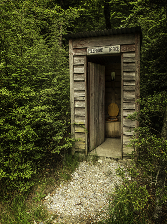 loo: an outhouse pretending to be a telephone booth Stock Photo