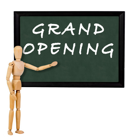mannequin pointing to blackboard with the text grand opening Imagens