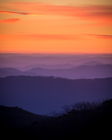 orange sunset sky with mountain ranges in the foreground