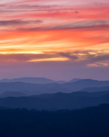 mountain ranges: orange sunset sky with clouds, mountain ranges in the foreground