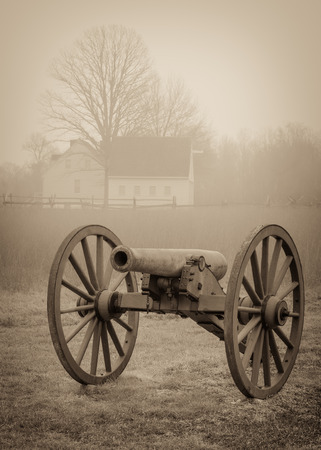 A civil war cannon with a farm house in the background at Cold Harbor