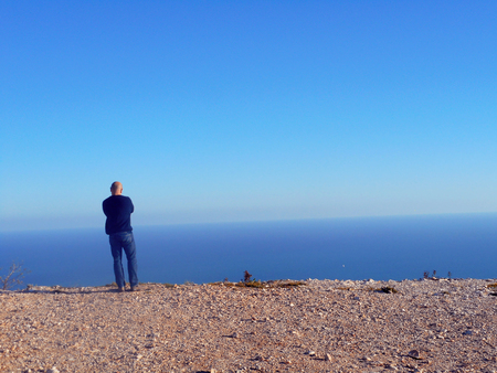 MAN LOOKING AT THE OCEAN BLUE SKY WITH AN AZURE Stock Photo