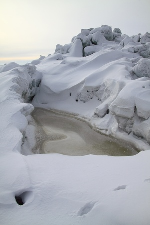 Small frozen lake in the hummoked ice Stock Photo - 10769514