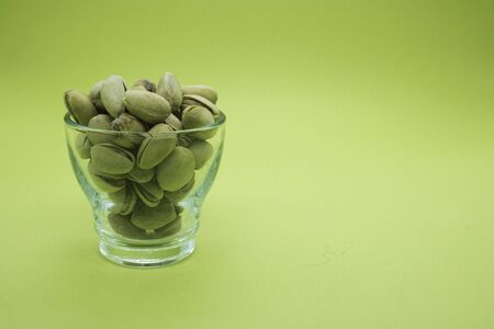 Pistachios in a glass bowl on a green background