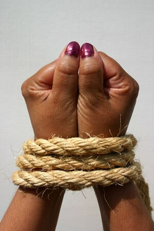hand held: Female hands bound with sisal rope, a conceptual image suggesting captivity