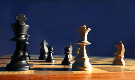 adversarial: Side lit image of a chess game