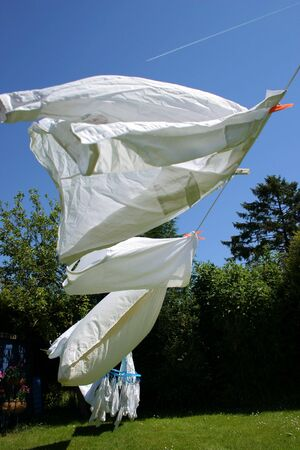 gust: White laundry drying on a hot and windy summer day Stock Photo