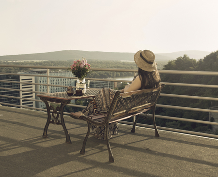 the distance: Woman Sitting at Balcony Looking to Distance Stock Photo