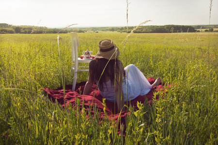 nostalgy: Woman Sitting Meadow Looking to Distance Stock Photo