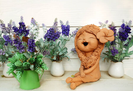 Clay doll and flower in ornamental garden photo
