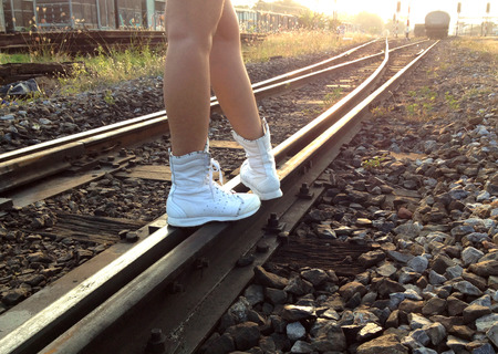 women in boots: Walking along the railroad in evening