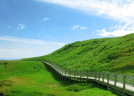 Wooden footpath to walk around green hill photo