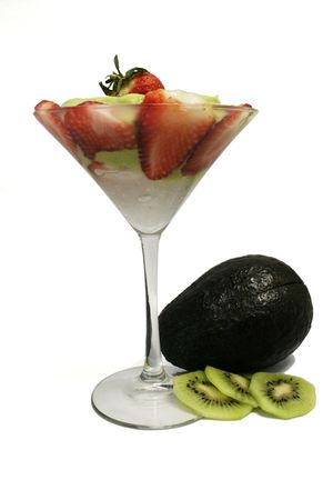 avocado juice covered with sliced strawberry decorated with whole avocado and sliced kiwi