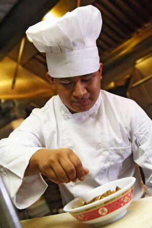 vegetable cook: il chef fa il tocco di rifinitura su alimento cinese