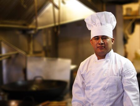 chef standing with blurred kitchen background Stock Photo