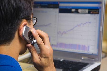 agente comercial: Agente de Bolsa llamando a su cliente al tiempo que busca en la computadora tabla de valores