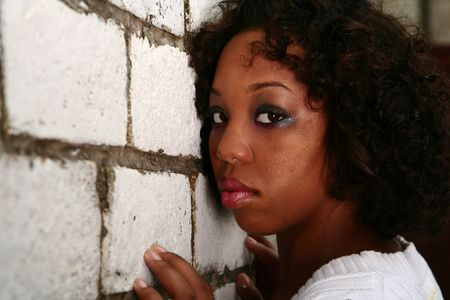 african american girl with innocent look showing blank expression leaning her face to white brick wall Stock Photo