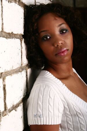 african american girl with innocent look showing blank expression leaning her back to white brick wall