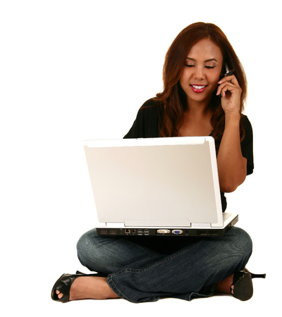 multi tasking: isolated shot of woman talking on the phone and working with laptop represent multi tasking Stock Photo