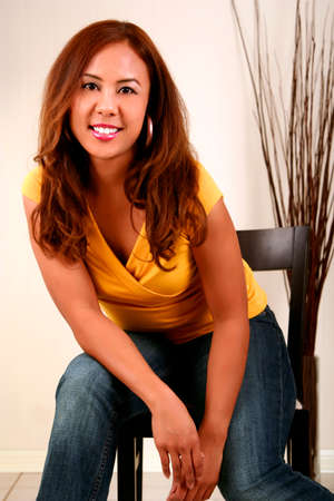 smoothen: fashion shot of pretty woman in yellow shirt posing on chair. skin was smoothen no noise reduction used Stock Photo