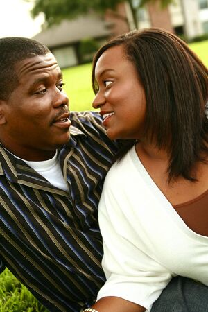 african american couple looking at each other with a house background