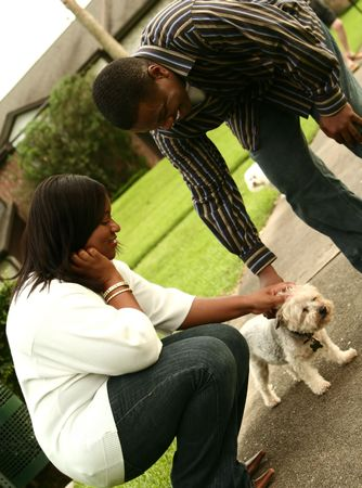 african american couple petting a dog photo