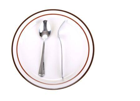 odd position of fork turn back on spoon placed on a dinner plate Reklamní fotografie