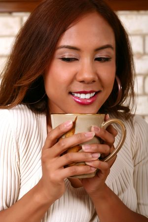 smoothen: beautiful model smelling her morning coffee. skin was smoothen no noise reduction used Stock Photo