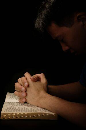 Las gracias de una elasticidad del hombre al dios que ruega con la biblia se abren Foto de archivo - 1985737