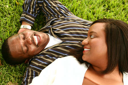 happy african american couple laying on the grass on a park