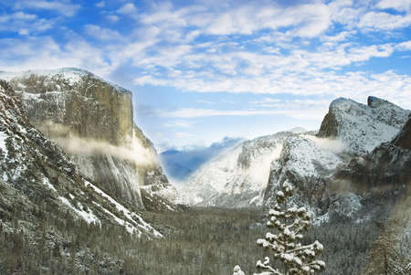 ansel adams famous tunnel view taken on winter season. some domes and trees are covered with snow photo