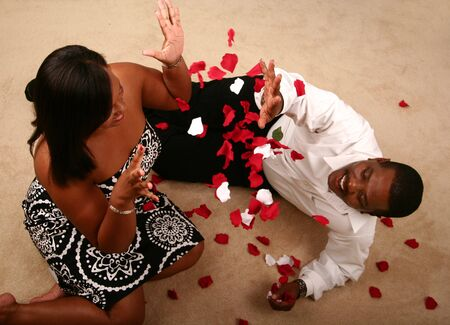 african american couple playing and throwing rose petal at each other