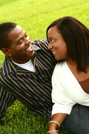 african american couple posing on the grass in an outdoor park