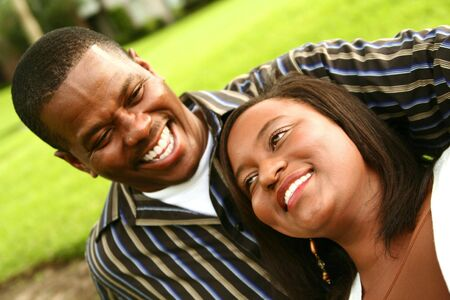 couple laughing: african american couple laughing while spending time together on the park. focus on woman Stock Photo