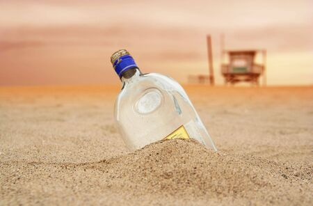 message bottle: a message bottle covered with beach sand and beach guards house on the background. sky showing sunsetting color Stock Photo