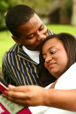 african american man kissing his wife who reading a book. focus on the woman photo