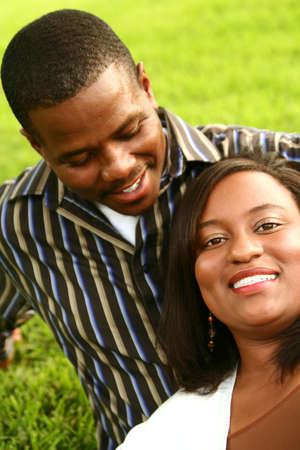 african american couple relaxing on the grass. the mant looking at his wife while she looking to the camera. focus on the woman Stock Photo