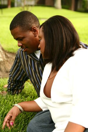 african american couple looking to the grass while relaxing on a park photo
