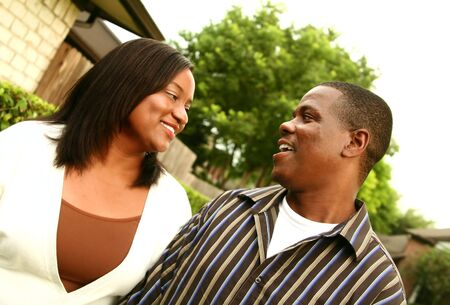 african american couple close up looking and smiling at each other while walking outdoor photo