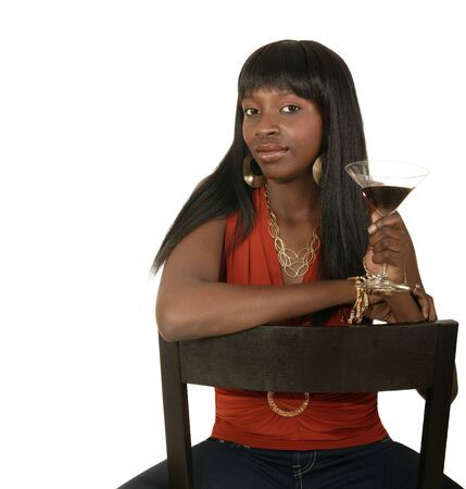 african american girl sitting on the chair while holding up drink from party 版權商用圖片