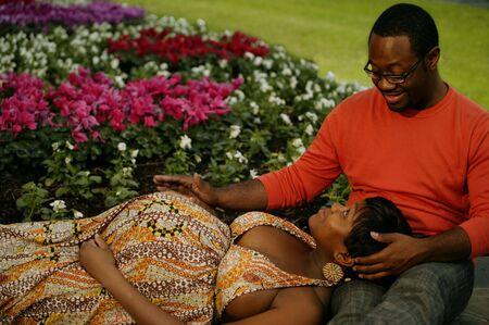 african american couple having conversation in a colorful flowers park