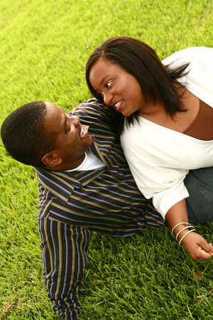 great composition of african american couple looking and smiling at each other on the grass in outdoor park