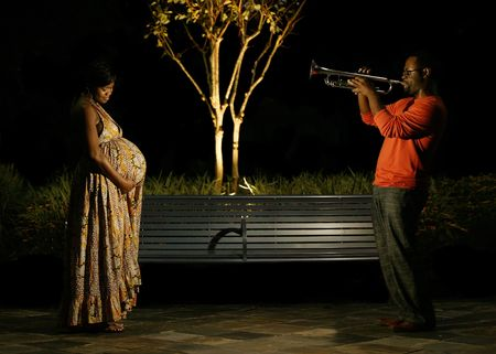 african american couple in outdoor park at night. the husband playing trumpet for his wife and the  in belly. great concept shot. there are little noise in certain area but barely noticeable