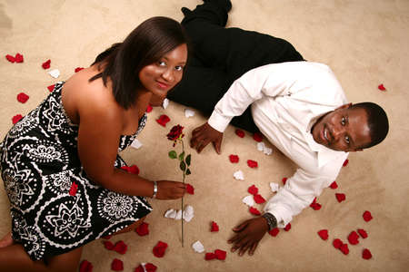 romantic african american couple sit and lay on the floor with rose petal around them photo