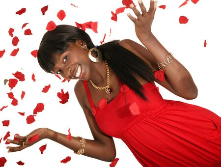 happy african american girl wearing hot red fashion dress throwing rose petal Stock Photo