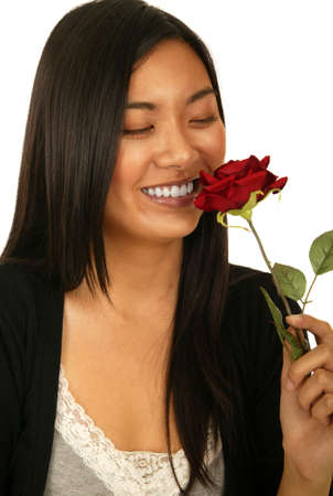 vietnamse: isolated shot of beautiful asian girl smelling rose with joy and happy expression Stock Photo