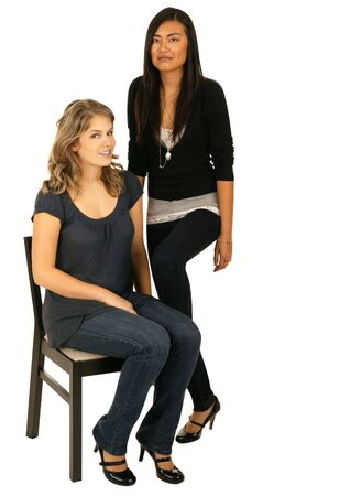 vietnamse: isolated caucasian girl sitting on a chair with her asian girl friend standing Stock Photo