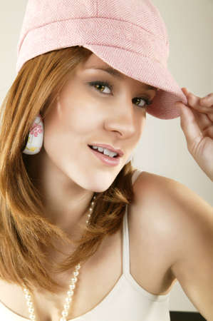 smoothen: high fashion shot of a caucasian girl with naughty look wearing pink hat. retouched to smoothen skin