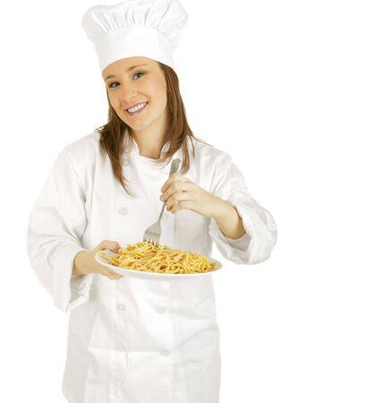 caucasian chef looking at camera while stirring pasta photo