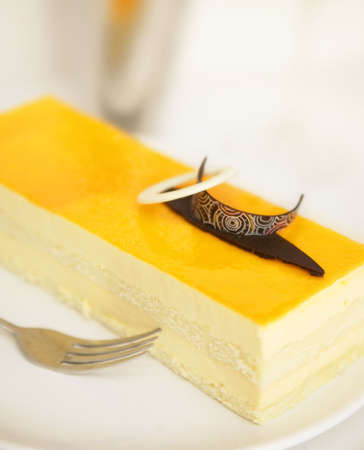 a dessert cake with mango flavor topped with unique design of chocolate
